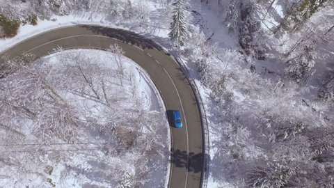 AERIAL: Flying above turquoise sport car driving through sharp bend in beautiful snowy forest in sunny winter wonderland. Amazing road trip through picturesque countryside nature in magical wintertime