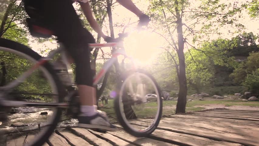 girl mountainbiker cycling on a wooden bridge over a river. slider shot