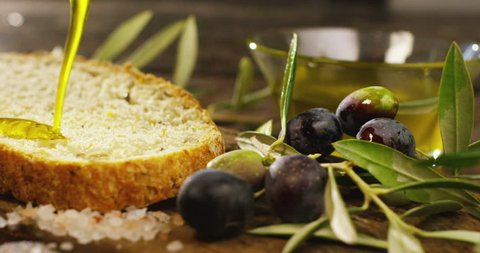 Genuine Italian organic oil cold pressed in slowmotion falls on organic bread. concept of nature and healthy food, healthy and natural. fresh olives and Tuscan Italian oil