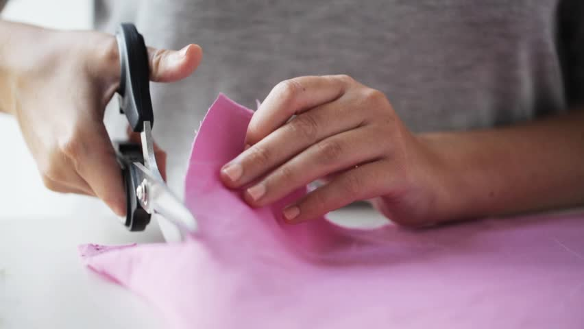people, stitching, needlework, sewing and tailoring concept - woman with tailor scissors or shears cutting out fabric at studio