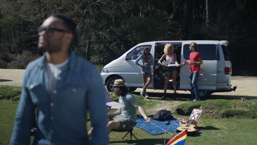 4k portrait of smiling hipster guy with friends in background at 4k portrait of smiling hipster guy with friends in background at music festival campsite shot voltagebd Image collections