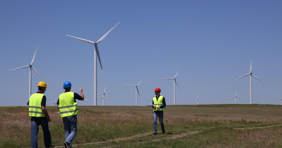 Engineer Men Teamwork Talking Alternative Energy Wind Turbines Crossing Field. Ultra High Definition, UltraHD, Ultra HD, UHD, 4K, 2160P, 4096x2160