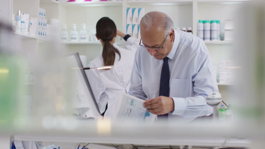 4K Workers in a chemist shop checking stock & discussing their work. Shot on RED Epic. | Shutterstock HD Video #20404261