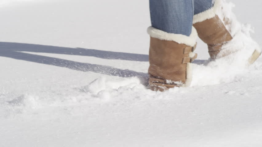 SLOW MOTION CLOSE UP: Unrecognizable female in jeans and warm winter boots walking in smooth deep snow blanket. Woman in sheepskin boots wading through fresh snow on a beautiful sunny Christmas day