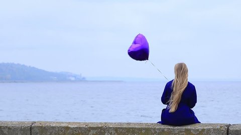 Upset young woman holding violet heart balloon.