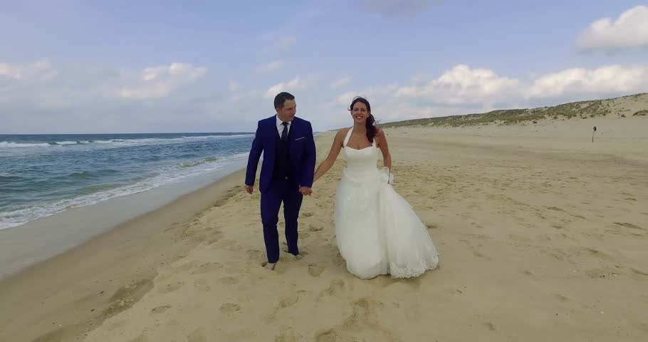 Happy Newly Wed Couple Walking On The Beach
