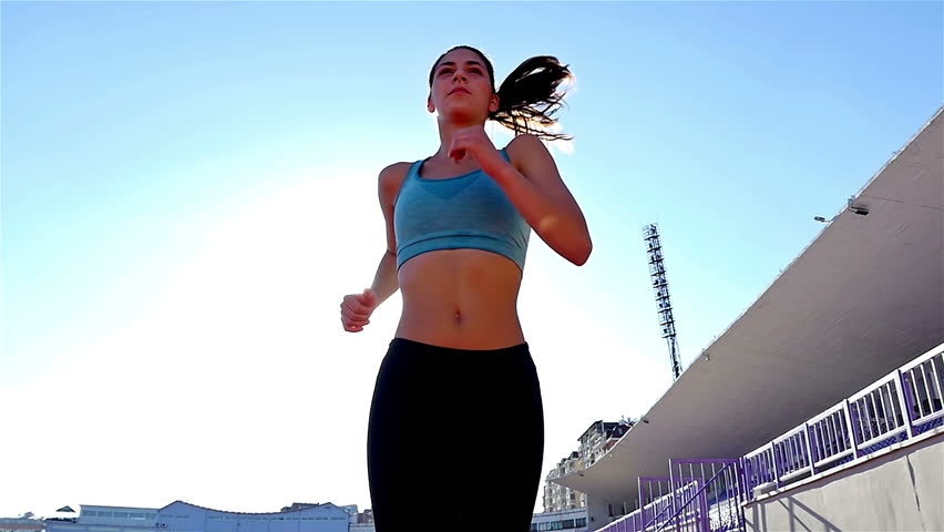Tracking camera of a track runner athlete woman girl running at a stadium, low angle, sun flare, slow motion