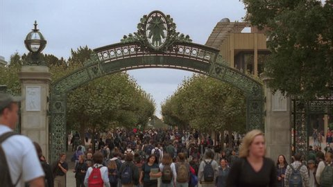 day across metal framed green arched entrance gate ND college university campus sea students mostly pants jackets fall winter entering campus University Berkeley