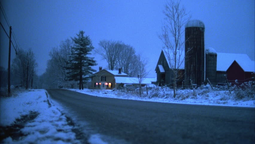late day dusk night low angle across snowy country road farm house country house lights barn grain silos then see SUV Jeep Wagoneer then another car cam , snow ground winter sky, Vermont,