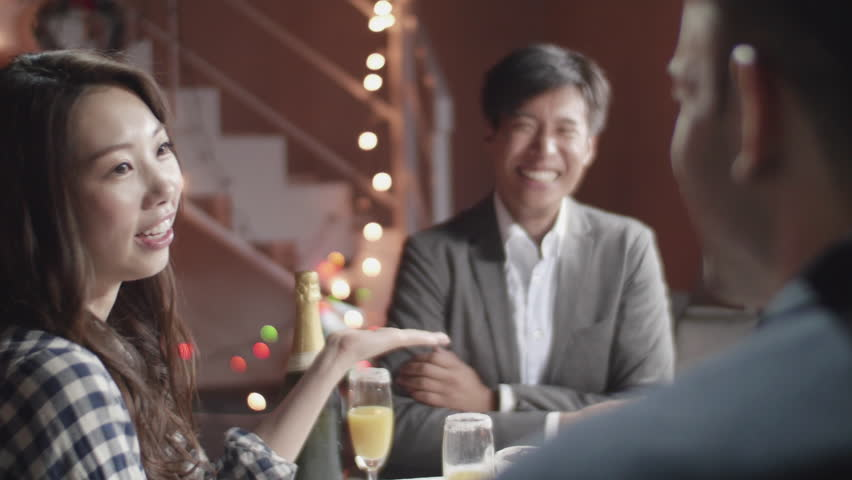 Beautiful Japanese women talks to two men at christmas dinner party