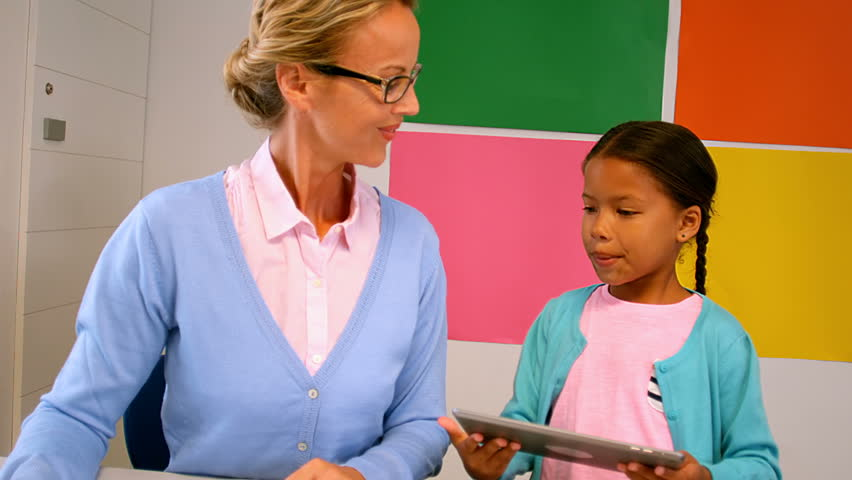 Front view of diverse schoolgirl and teacher using digital tablet in classroom at school | Shutterstock HD Video #20528971