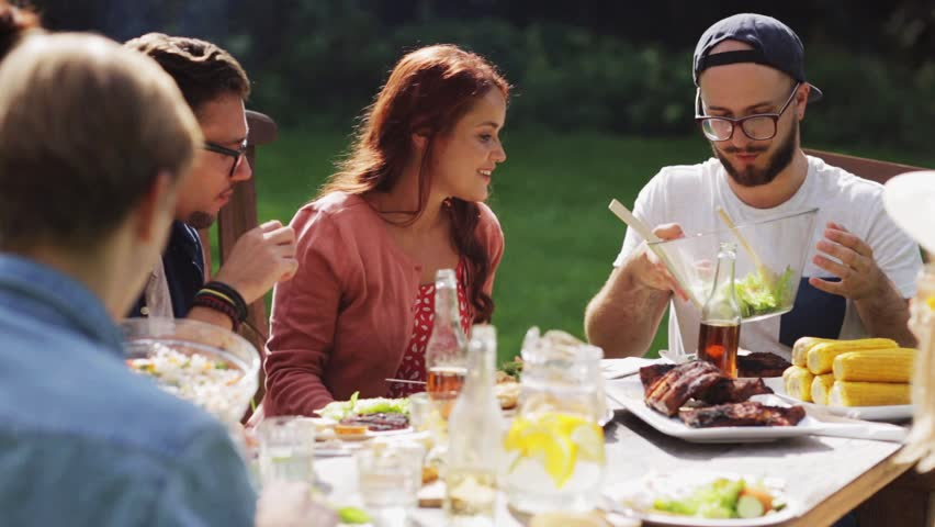 Leisure, holidays, eating, people and food concept - happy friends having dinner at summer garden party | Shutterstock HD Video #20553106