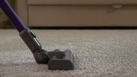 A woman uses a vacuum cleaner to clean the carpet.