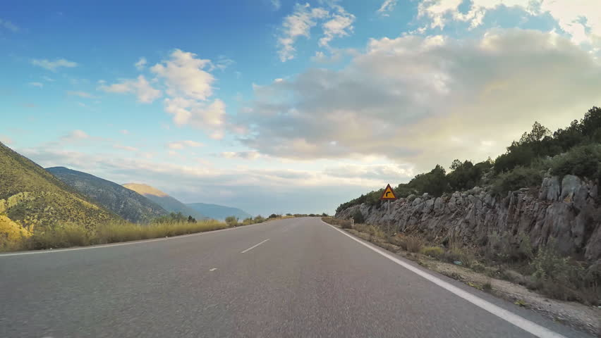 Point of view vehicle drive car travel countryside road rocky hilly scenery clouds blue sky day POV
