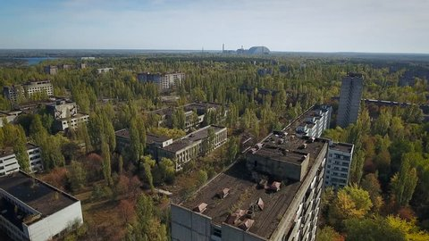 Flyover main square of Pripyat Town after meltdown of the Chernobyl nuclear power plant in 1986. Reactor & new sarcophagus on horizon. Polyissa Hotel, restaurant, supermarket are seen. Oct. 2016.