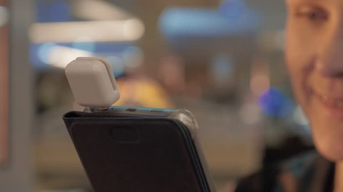 Close up view of smartphone in woman hands with special dongle for paying card. Unfocused smiling face of woman on the background