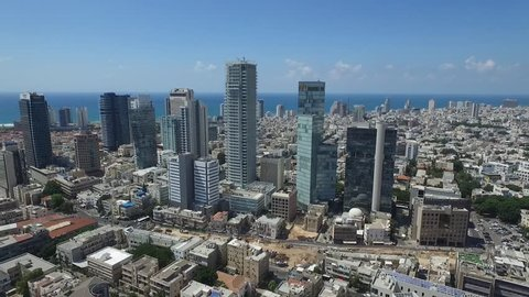 Aerial view of tall commercial buildings with the city skyline and the sea in the background  Epic shot of Rothschild Blvd. in Tel Aviv Israel the river, ending at city skyline Amazing aerial shot!