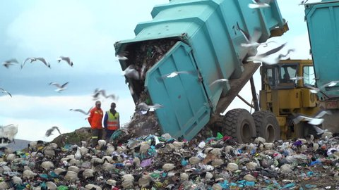 truck offloading waste into a huge landfill