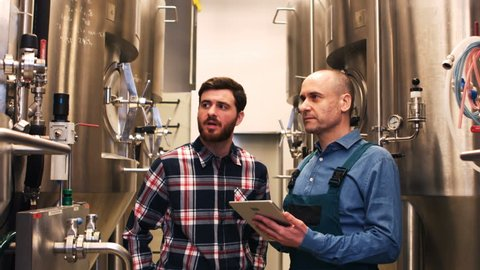 Brewers maintaining record on digital tablet at brewery
