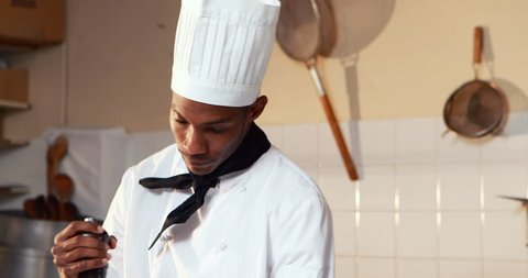 Chef sprinkling pepper on a meal in commercial kitchen 4k