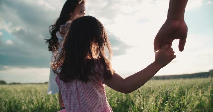little Asian girl walking on the green field with their parents, holding hands, slow motion