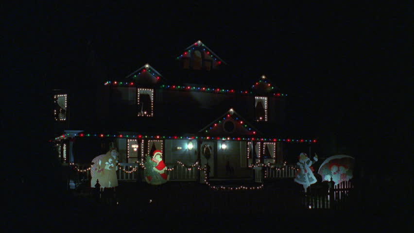 night left nice two story house multicolored Christmas lights, attic, lighted lawn art scrooge next Mrs. Claus others then pans left along residential street all houses Christmas decoration