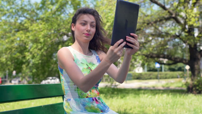 Pretty girl sitting in the park and doing selfies on tablet , HD stock  footage clip