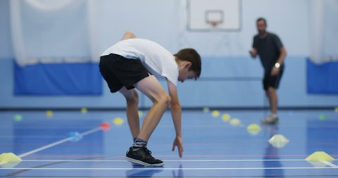 4K Sports teacher coaching young boy, running laps & working hard in school gym