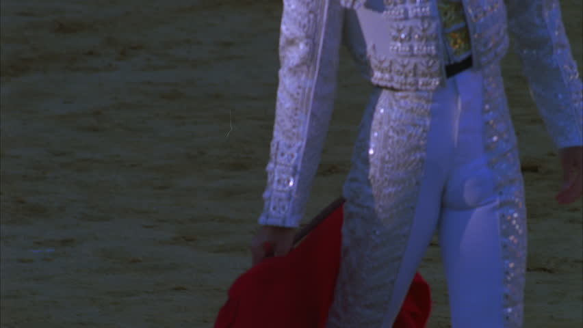 day tight matador shaking red cape, bull lances handing from bloody shoulders, runs through bull Bullfighting, Spain