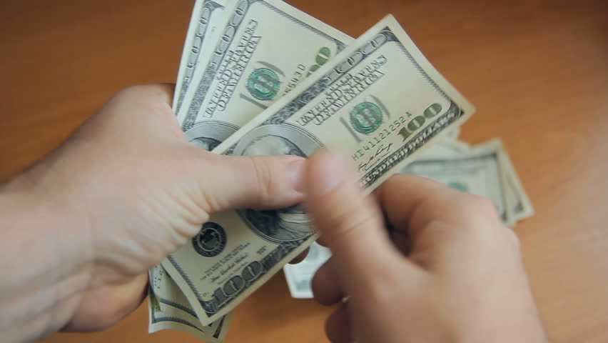 person counts the money. Dollars in hand, money in hand, counts the money