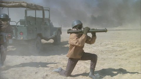 day desert battle scene soldier knee RPG rocket propelled grenade launcher weapon other soldiers rifles shooting right, military convoy driving around, some fall ground then get up, middle