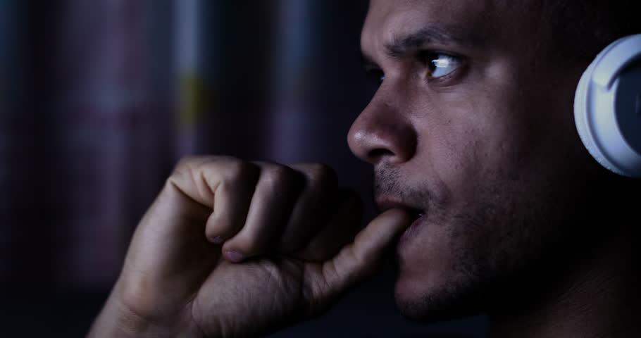 4K Man at night with headphones watching a screen and biting his nails