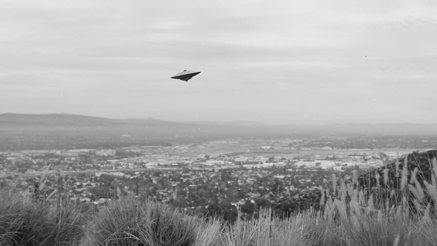 FLYING SAUCER OVER LOS ANGELES.  VINTAGE-LOOKING FOOTAGE OF A UFO ABOVE A VAST VALLEY BELOW.  BLACK & WHITE.