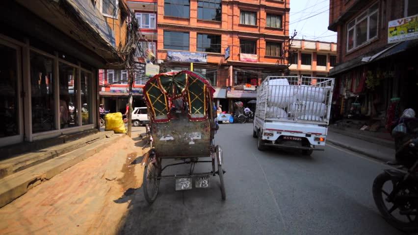 KATHMANDU, NEPAL - APRIL 8, 2016: Streets of Thamel. Cars, walking people, rickshaws cycles, busy crossroad. In 2013, Kathmandu was ranked third among the top 10 travel destinations in the world