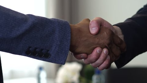 We see a handshake between two businessmen. The agreement between them had been reached. One of them is an African American/Handshake of Two Businessman - is the Completion of the Transaction