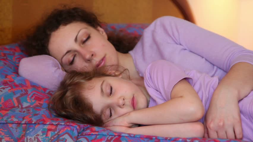 Mother and her little daughter sleep on bed, then they wakes and mom kiss girl, closeup view