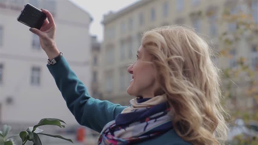 Girl Recieve Videocall. Happy woman having a videocall on smartphone in the city
