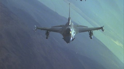 day Air to Air ing two F 16 Falcon fighter jets See third F 16 beginning Over desert terrain playback