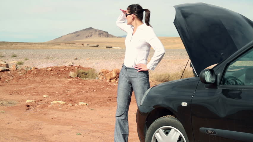 Upset businesswoman by the broken car, outdoors