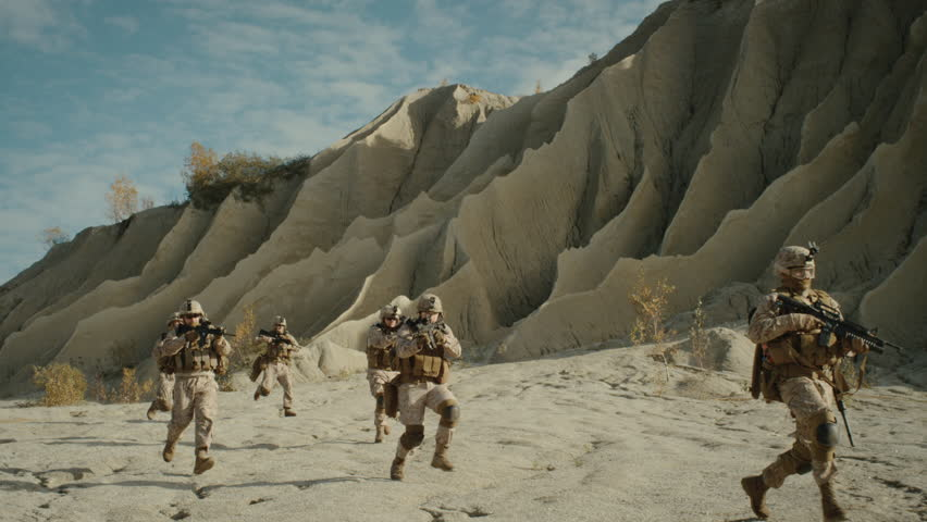 Squad of Fully Equipped, Armed Soldiers Running and Attacking During Combat in the Desert. Slow Motion. Shot on RED EPIC Cinema Camera in 4K (UHD).