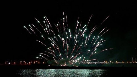 Green, red and White fireworks over the sea at night in Barcelona.Slow motion