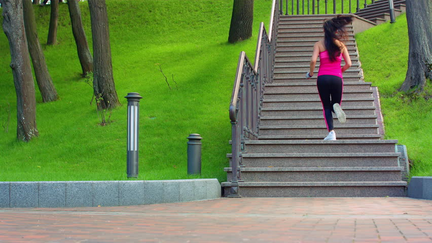 Sporty woman running up stairs at park. Fitness model running upstairs in slow motion. Young woman climbing stairs. Athletic woman run up stairs