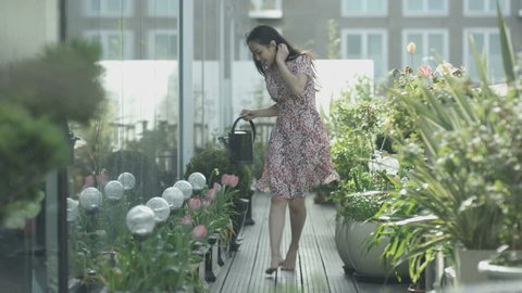 4K Attractive young woman watering plants in city rooftop garden