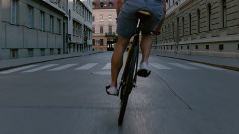Behind young man swerving with his bicycle in the middle of the city street
