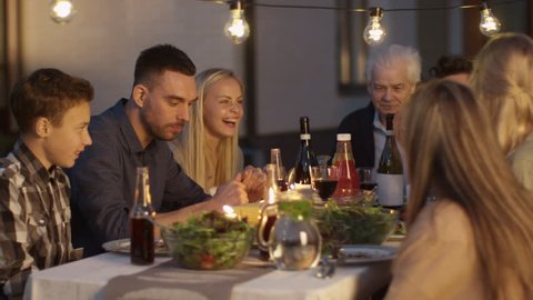 Group of People Sitting Around a Table, Eating, Communicating and Having Fun during Family Gathering Dinner. Shot on RED Cinema Camera in 4K (UHD).