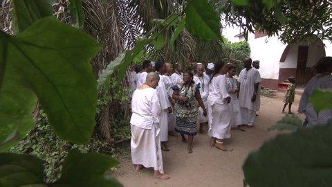 Lagos, Nigeria - August 2013; Women and men dressed in white walk towards Orisha initiation house.