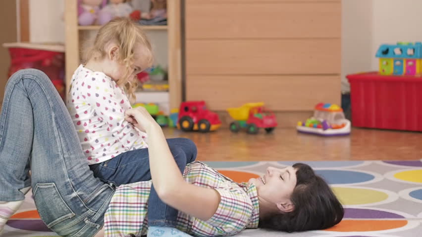 Young Mother Holding Her little girl daughter in the room lying on the floor.
