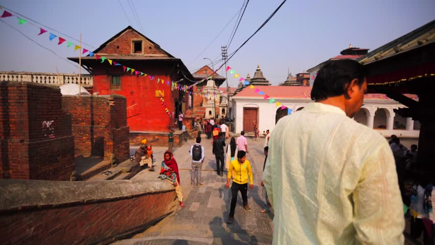 KATHMANDU, NEPAL - APRIL 11, 2016: View of square in Pashupatinath Temple, one of the sacred temples of Hindu faith. Hindu monk blesses little girl.