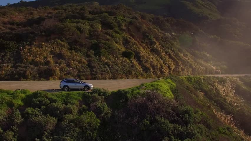 Aerial revolving shot of a Subaru car parked on the side of a cliff overlooking the ocean in Big Sur, California. Dazzling sunlight with fog and mist down the coast.
