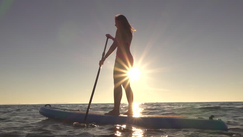 SLOW MOTION CLOSE UP: Pretty woman standing on inflatable SUP board and paddling through soft ocean shining ocean surface. Active sporty girl enjoying vacation riding the paddleboard on sunny morning
